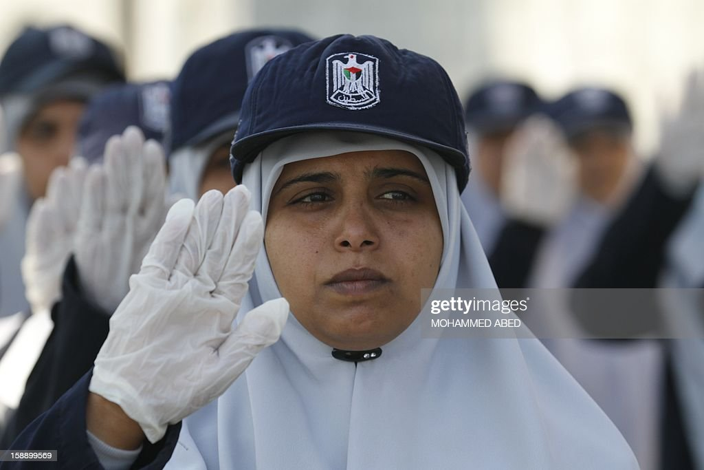 A Palestinian female graduate member of Hamas' national security forces gestures during a parade as part of a graduation ceremony in Gaza City on January 3, 2013.