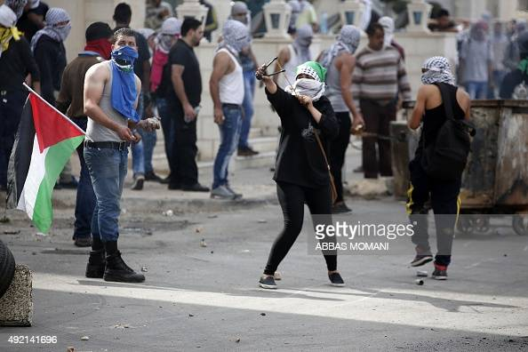 A Palestinian female protester uses a slingshot to throw stones during clashes with Israeli security forces in Beit El Jewish settlement north of...