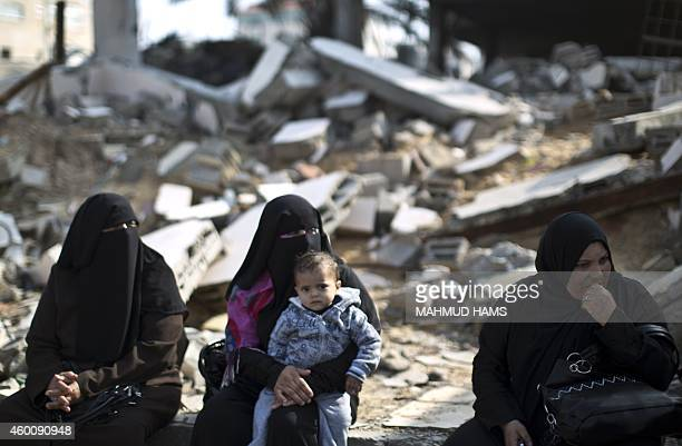 Palestinian female supporters of the Popular Front for the Liberation of Palestine sit next of damaged building during a protest against the delay in...