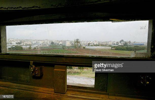 Palestinian fields and homes are seen through the armored glass and sniper's window of a sentry box built into the 26foot high reinforced concrete...