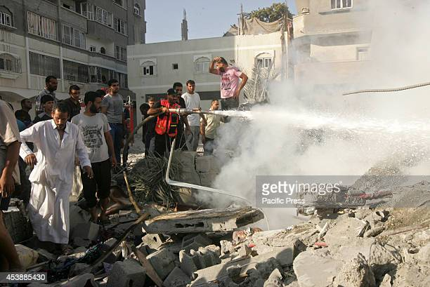 Palestinian fire fighter drags a hose to the part of a burning house hit by an Israeli airstrike at Rafah in the South of the Gaza Strip There is no...