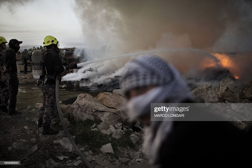 Palestinian fire fighters battle flames that erupted in a Bedouin encampment during clashes between Palestinian stone throwers and Israeli security forces in the West Bank village of Anata on March 8, 2013.