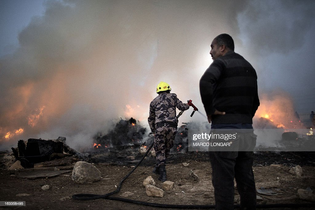 Palestinian fire fighters battle flames that erupted in a Bedouin encampment during clashes between Palestinian stone throwers and Israeli security forces in the West Bank village of Anata on March 8, 2013. AFP PHOTO/MARCO LONGARI