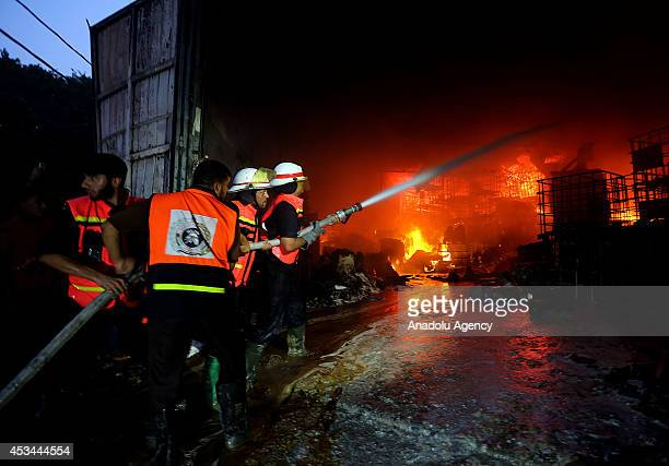 Palestinian fire fighters try to extinguish a fire broke out at a factory producing cleaning supplies and hit by an Israeli attack in Rimal...