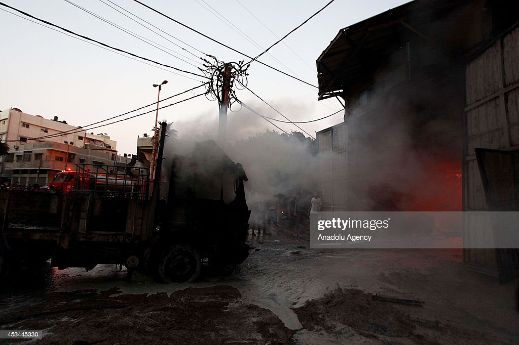 Palestinian fire fighters try to extinguish a fire broke out at a factory, producing cleaning supplies and hit by an Israeli attack in Rimal neighborhood of Gaza City, Gaza on August 10, 2014.