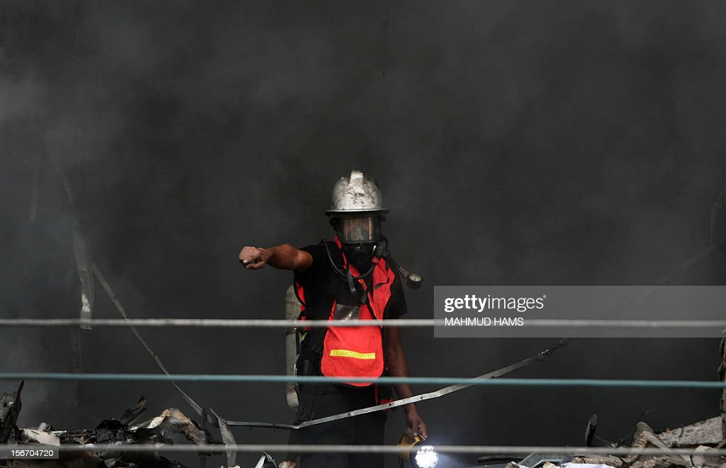 A Palestinian firefighter gestures during a blaze following an Israeli air strike on the Gaza City tower housing Palestinian and international media, on November 19, 2012. Israeli air strikes killed 21 Palestinians hiking the Gaza death toll to 98 as global efforts to broker a truce to end the worst violence in four years gathered pace. AFP PHOTO/MAHMUD HAMS