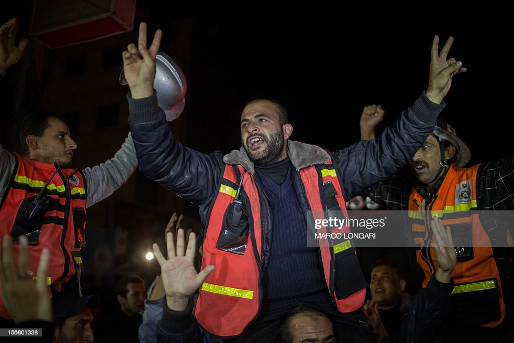Palestinian firefighters celebrate the beginning of the truce with Israel in Gaza City on November 21, 2012. Palestinians in Gaza took to the streets to celebrate the start of a truce deal with Israel that was announced in Egypt on the eighth day of violence in and around Gaza. AFP PHOTO/MARCO LONGARI