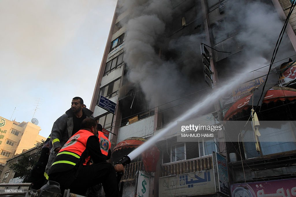 Palestinian firefighters extinguish a blaze following an Israeli air strike on the Gaza City tower housing Palestinian and international media, on November 19, 2012. Israeli air strikes killed 21 Palestinians hiking the Gaza death toll to 98 as global efforts to broker a truce to end the worst violence in four years gathered pace. AFP PHOTO/MAHMUD HAMS