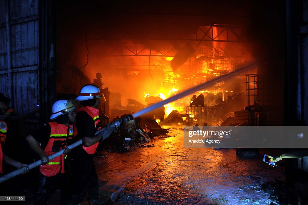 Palestinian firefighters extinguish a factory hit by Israeli assaults at the El Mina Street in Gaza City, Gaza on August 10, 2014.
