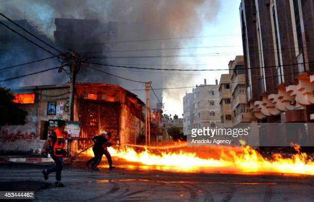 Palestinian firefighters extinguish a factory hit by Israeli assaults at the El Mina Street in Gaza City Gaza on August 10 2014