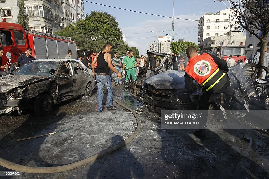 Palestinian firefighters extinguish fire from a car after it was hit by an Israeli air strike in Beit Lahia, northern of Gaza Strip, on November 19, 2012. Air strikes across the Gaza Strip killed 18 people, raising the Palestinian death toll to 95 on the sixth day of a relentless Israeli aerial campaign. AFP PHOTO/MOHAMMED ABED
