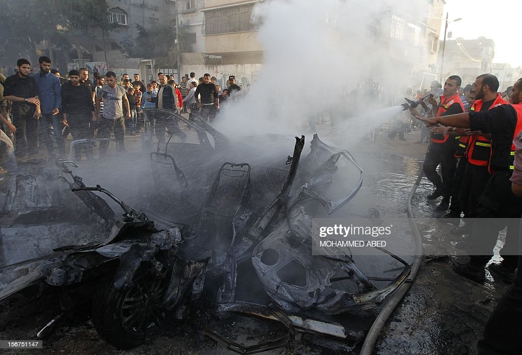 Palestinian firefighters extinguish fire from a vehicle following an Israeli strike in Gaza City on November 20, 2012. Israel's air force dropped leaflets across several districts of Gaza City urging people to evacuate their homes 'immediately' amid fears of an imminent ground invasion.
