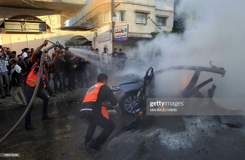 Palestinian firefighters extinguish fire from the car of Ahmaed Jaabari, head of the military wing of the Hamas movement, the Ezzedin Qassam Brigades, after it was hit by an Israeli air strike in Gaza City on November 14, 2012. The top Hamas commander Ahmed al-Jaabari was killed in an Israeli air strike , medics and a Hamas source told . AFP.
