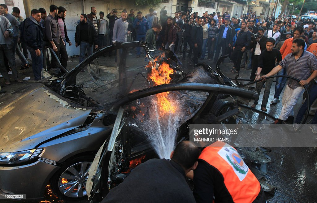 Palestinian firefighters extinguish fire from the car of Ahmaed Jaabari, head of the military wing of the Hamas movement, the Ezzedin Qassam Brigades, after it was hit by an Israeli air strike in Gaza City on November 14, 2012. The top Hamas commander Ahmed al-Jaabari was killed in an Israeli air strike , medics and a Hamas source told . AFP PHOTO/MAHMUD HAMS