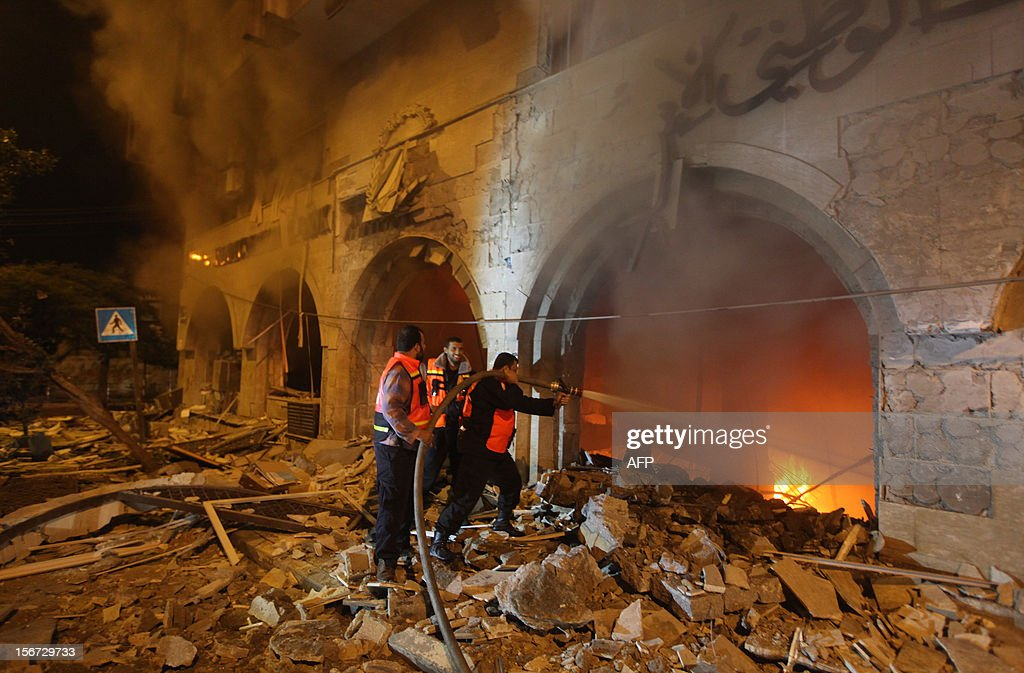Palestinian firefighters try to extinguish a blaze after an Israeli air strike on the Islamic National Bank building in Gaza City on November 20, 2012. Israeli leaders discussed an Egyptian plan for a truce with Gaza's ruling Hamas, reports said, before a mission by the UN chief to Jerusalem and as the toll from Israeli raids on Gaza rose over 100. AFP PHOTO/MAJDI FATHI