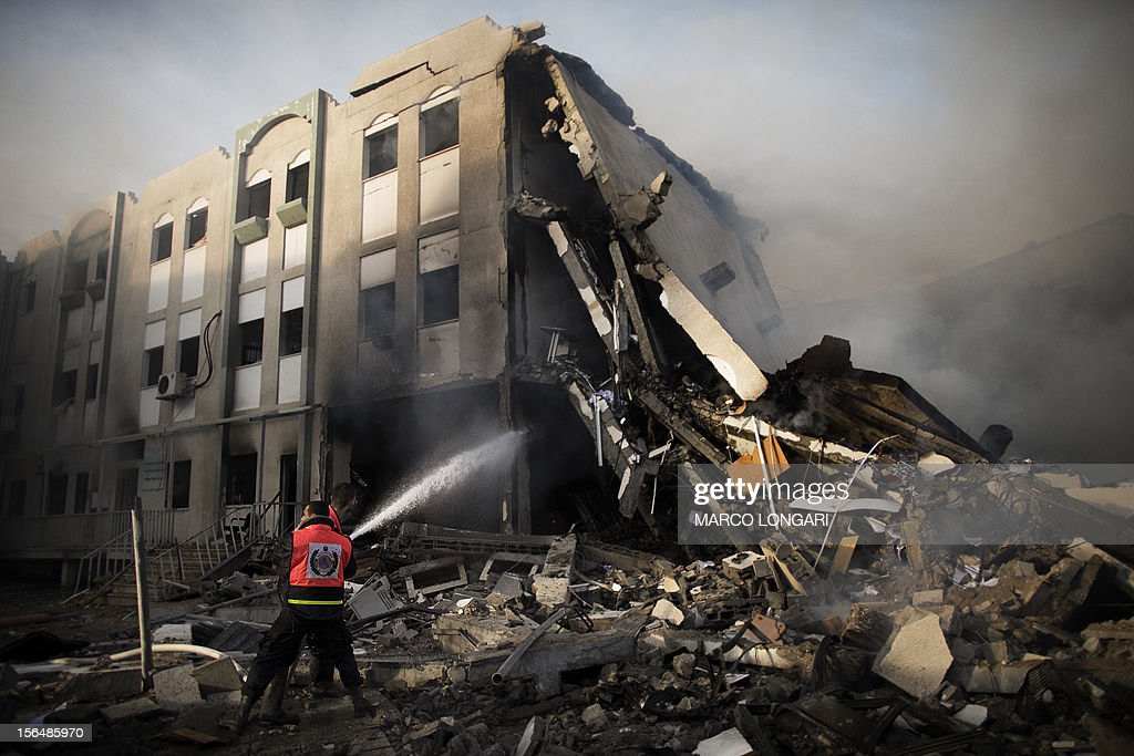 Palestinian firefighters try to extinguish a fire at the Civilian Affairs branch of the Ministry of Interior following an Israeli air raid in Gaza City on November 16, 2012. Israel was condemned by much of the Arab world while securing Western backing and pressing its biggest air assault on Gaza for years amid a wave of Palestinian short-range rocket fire. AFP PHOTO/MARCO LONGARI