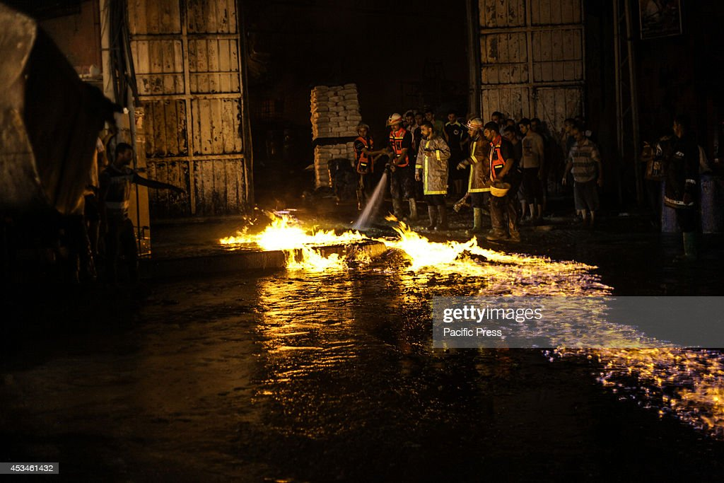 Palestinian firefighters try to extinguish a fire in a factory for chemicals in the west of Gaza City because of an Israeli air strike, the bombing came after the approval of the Palestinians and Israelis on the Egyptian-brokered truce for 72 hours to stop the fire between the two sides.