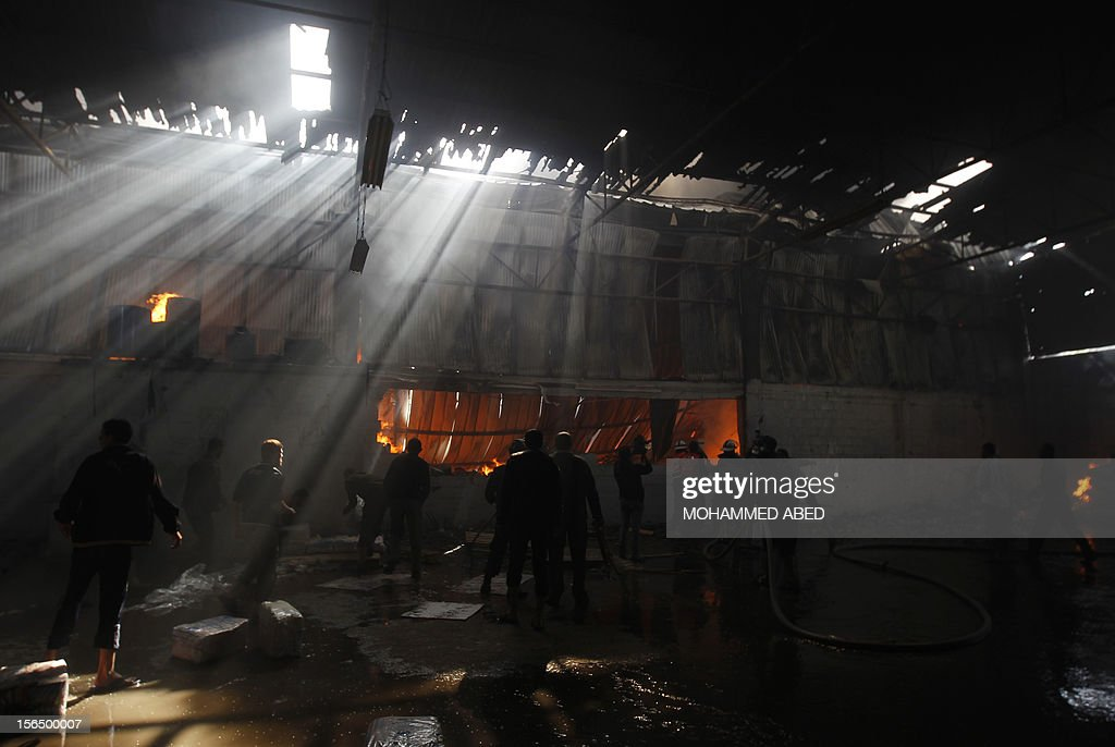 Palestinian firefighters try to extinguish fire at a factory, which according to locals was hit by an Israeli air strike in Beit Lahia, northern Gaza Strip, on November 16, 2012. Egypt's premier vowed to intensify Cairo's efforts to secure a truce and urged world leaders to end Israel's 'aggression' in Gaza, as he visited the Hamas-run enclave. AFP PHOTO/MOHAMMED ABED