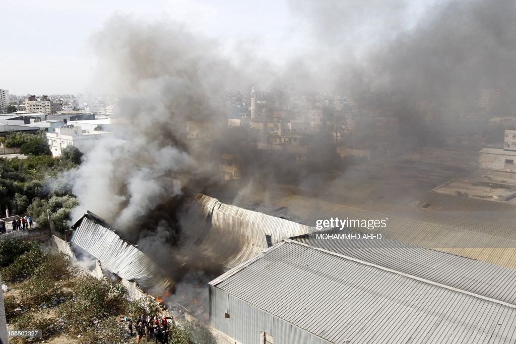 Palestinian firefighters try to extinguish fire at a factory, which according to locals was hit by an Israeli air strike in Beit Lahia, northern Gaza Strip, on November 16, 2012. Egypt's premier vowed to intensify Cairo's efforts to secure a truce and urged world leaders to end Israel's 'aggression' in Gaza, as he visited the Hamas-run enclave. AFP PHOTO/MOHAMMED