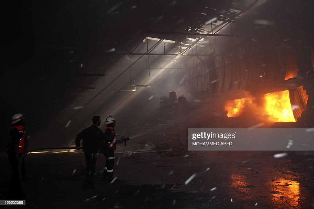 Palestinian firefighters try to extinguish fire at a factory, which according to locals was hit by an Israeli air strike in Beit Lahia, northern Gaza Strip, on November 16, 2012. Egypt's premier vowed to intensify Cairo's efforts to secure a truce and urged world leaders to end Israel's 'aggression' in Gaza, as he visited the Hamas-run enclave.