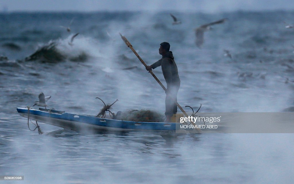 A Palestinian fisherman goes to the sea during a rainy weather on February 8, 2016 in Gaza city. / AFP / MOHAMMED ABED