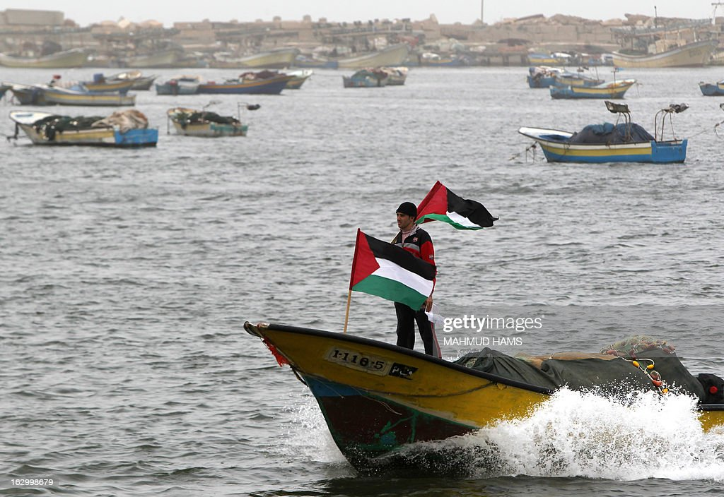 A Palestinian fisherman holds his national flag as he rides a boat off the coast of Gaza City during a protest against Israeli military attacks on fishing boats on March 3, 2013. Israel imposes a strict maritime blockade of the Gaza Strip, restricting the access of Palestinian fishermen. AFP PHOTO / MAHMUD HAMS