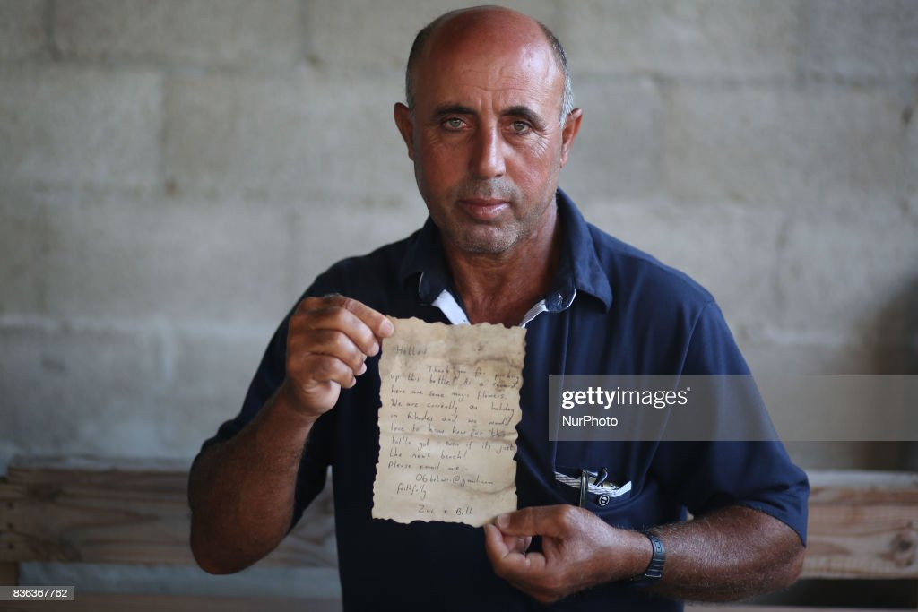 Palestinian fisherman Jihad al-Soltan displays a message that was written by Bethany Wright and her boyfriend Zac Marriner, after he found it in a bottle off a Gaza beach, in Gaza August 21, 2017. The Gazan fisherman says he contacted Bethany and Zac in greech who expressed being happy their message reachea Gaza and they pass their regarda to Palestinian people. Bethany and Zac have been contacted by joutnalists to find the origin of this message in a bottle story. They sent him photos of them through email. They said they are happy their message reached Gaza.