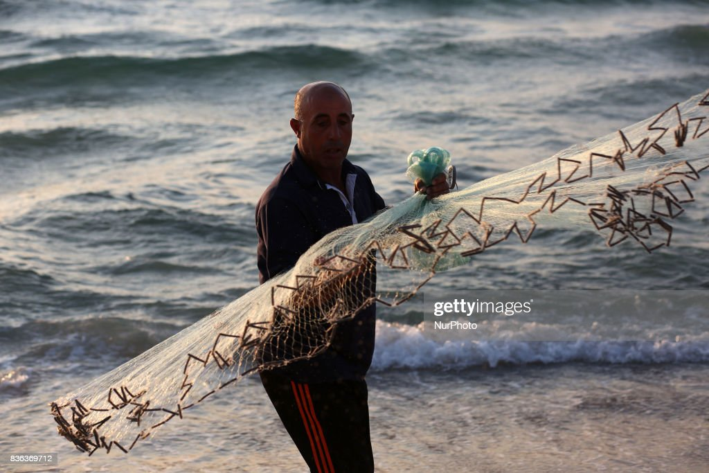 Palestinian fisherman Jihad al-Soltan (R) prepares his fishing net on a beach in the northern Gaza Strip August 21, 2017. The Gazan fisherman says he contacted Bethany and Zac in greech who expressed being happy their message reachea Gaza and they pass their regarda to Palestinian people. Bethany and Zac have been contacted by joutnalists to find the origin of this message in a bottle story. They sent him photos of them through email. They said they are happy their message reached Gaza.