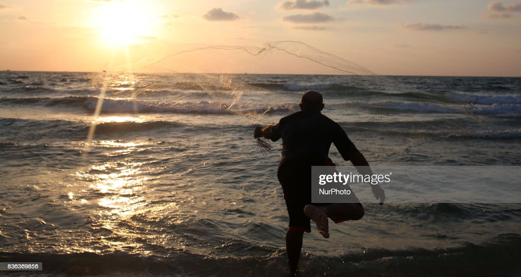 Palestinian fisherman Jihad al-Soltan (R) prepares his fishing net on a beach in the northern Gaza Strip August 21, 2017.