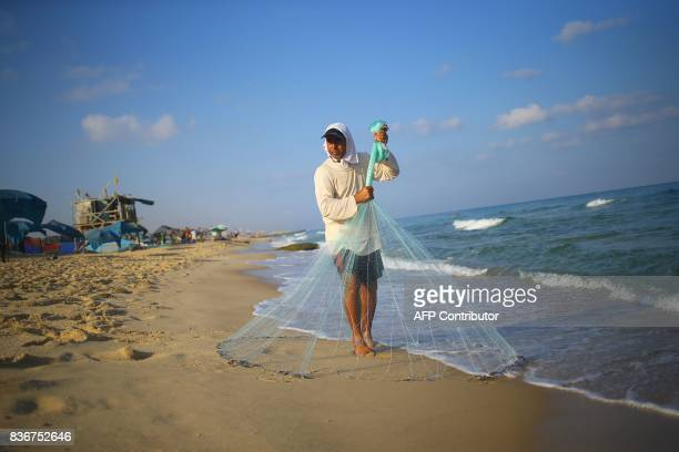 Palestinian fisherman Jihad alSoltan prepares to throw his fishing net on a beach in Beit Lahia in the northern Gaza Strip on August 22 2017 Soltan...