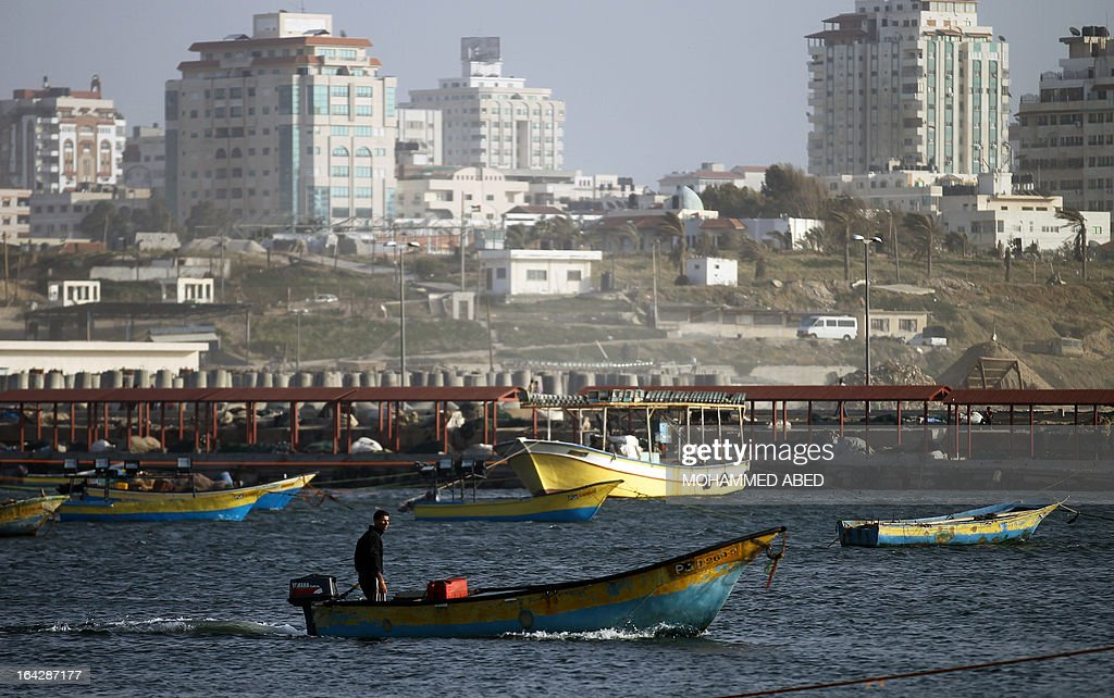 A Palestinian fisherman rides a boat near the port of Gaza City on March 22, 2013. Israel cut the distance from the shore that Gaza fishermen are allowed to sail from six to three miles and shut the Kerem Shalom goods crossing from Israel into the Gaza Strip in response to a rocket attack against southern Israel.
