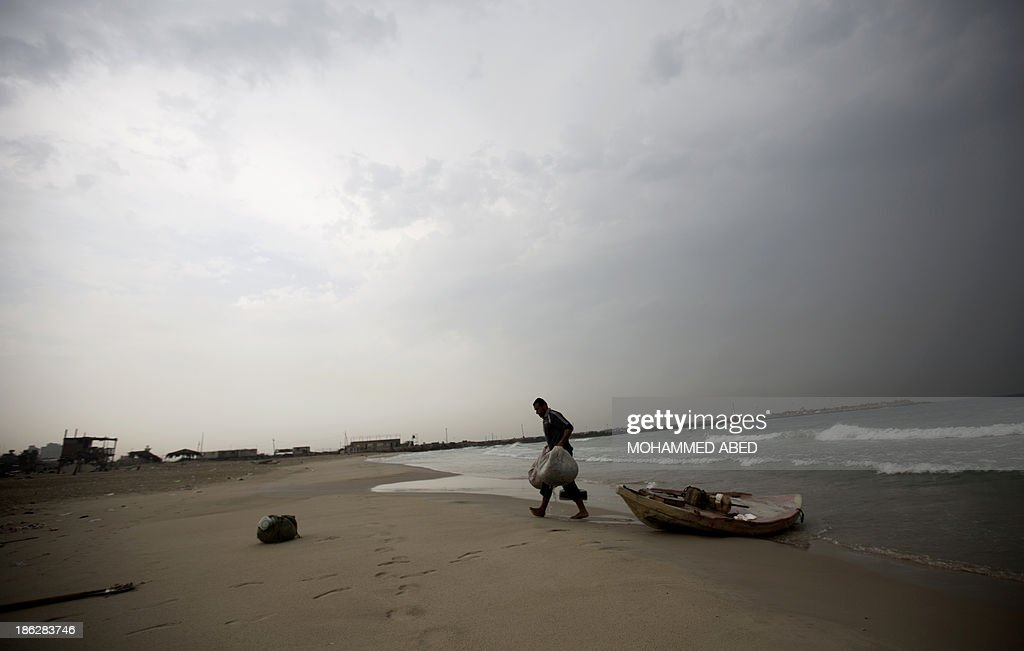 A Palestinian fisherman unloads his boat on a beach in Gaza City on October 30, 2013.