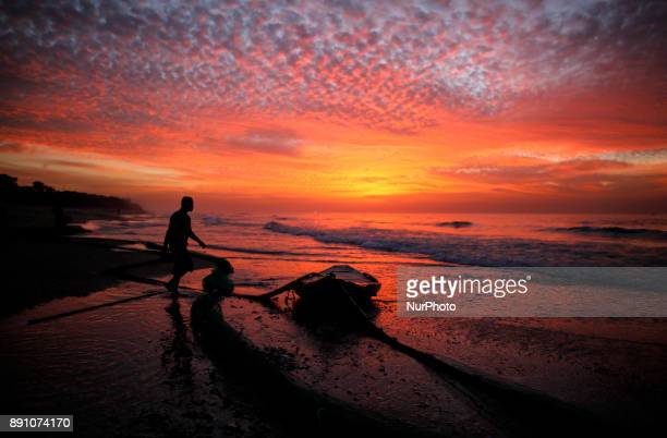 A palestinian fisherman walks next to his boat on the beach of Gaza City during sunset December 12 2017
