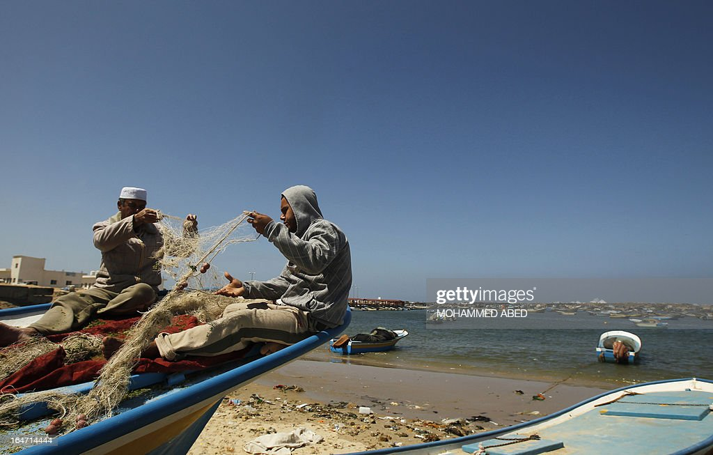 Palestinian fishermen fix their nets in the port of Gaza City on March 27, 2013. An Israeli military spokesman announced on March 21, that the Israeli military will again reduce the permitted fishing range in the Gaza Strip from six nautical miles to three (approximately 5.5 kilometres), in response to missile fire by armed Palestinian groups towards the south of Israel earlier that morning.