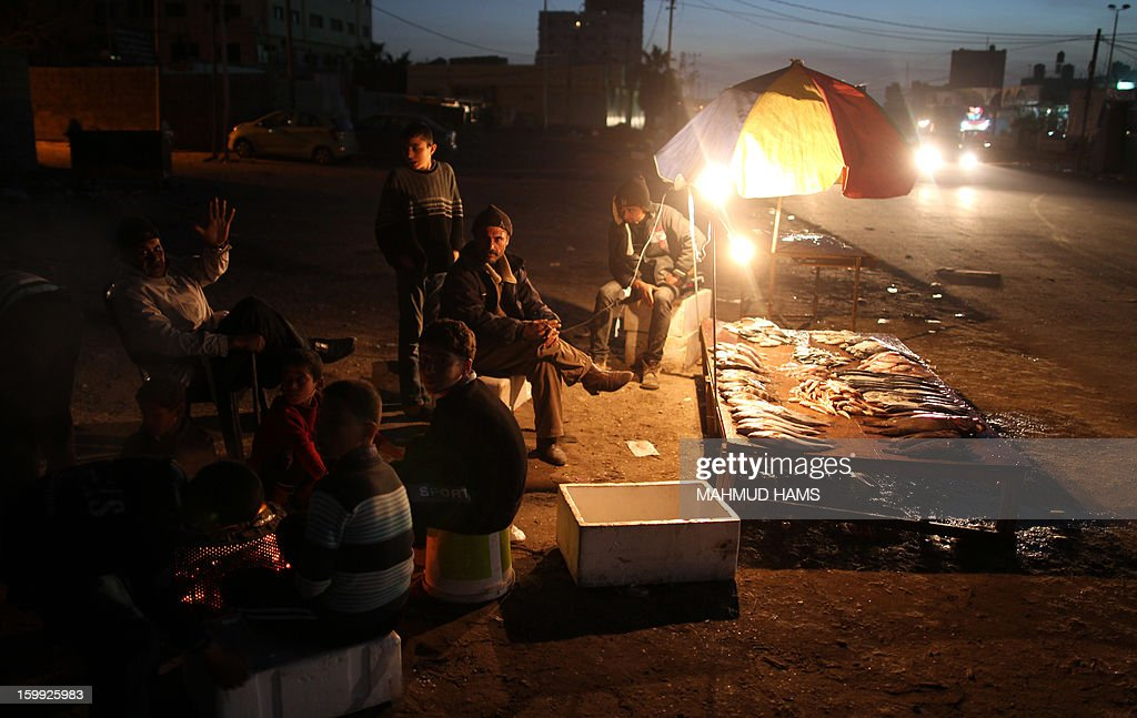 Palestinian fishermen sell fish on the beach front after their return from the sea in Gaza City on January 23, 2013. Palestinian fishermen have restricted access to the sea and are closely monitored by Israeli naval forces which regularly fire warning shots at fishing boats off the coast of the blockaded Gaza Strip. AFP PHOTO / MAHMUD HAMS