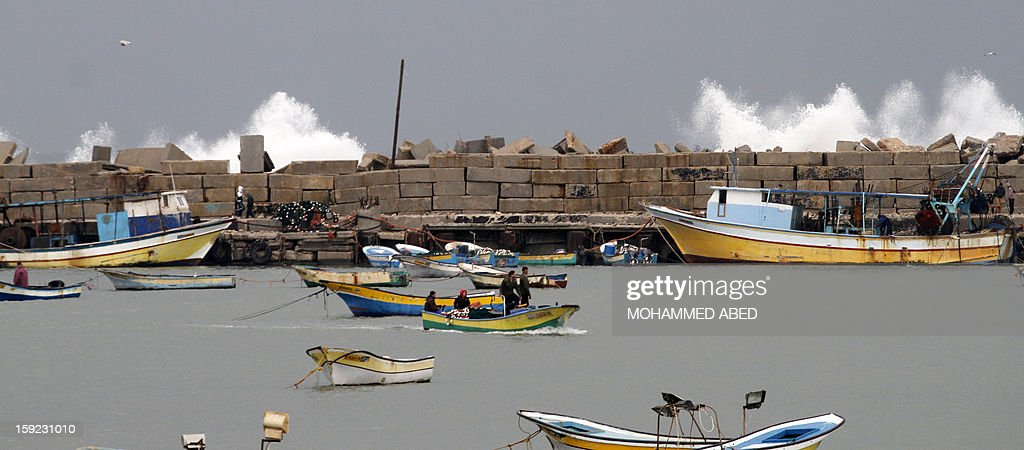 Palestinian fishermen stand on their boat in front of giant waves walks on January 10, 2013 in Gaza City. In Gaza, cold weather and heavy rain flooded several of the tunnels running between the territory and Egypt as in the West Bank city of Ramallah, children and adults, including some policeman stopped their cruiser for an impromptu snowball fight.