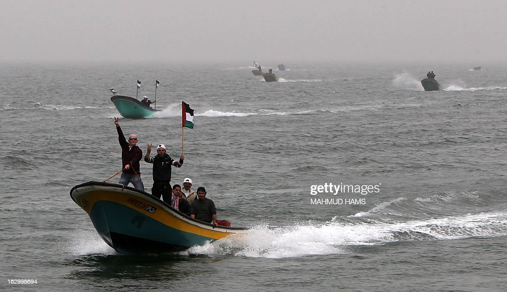 Palestinian fishermen wave their national flag as they ride a boat off the coast of Gaza City during a protest against Israeli military attacks on fishing boats on March 3, 2013. Israel imposes a strict maritime blockade of the Gaza Strip, restricting the access of Palestinian fishermen. AFP PHOTO / MAHMUD HAMS