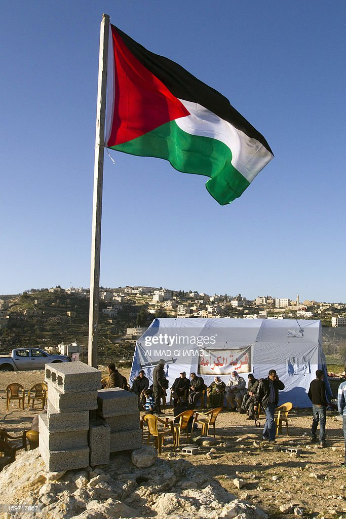 A Palestinian flag flies near Palestinian protestors as they gather next to tents erected in the West Bank village of Beit Iksa, between Ramallah and Jerusalem, on January 19, 2013. Some 200 Palestinians gathered at the new encampment protesting for the second consecutive day Israel's intention to confiscate land. AFP PHOTO/AHMAD GHARABLI
