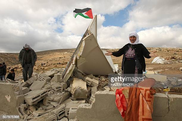 A Palestinian flag flies on top of the rubble of a woman's home who reacts after Israeli bulldozers demolished her house in a disputed military zone...