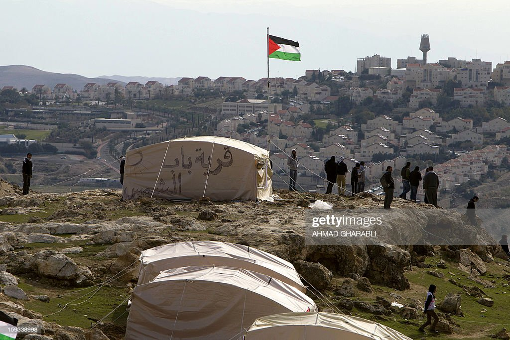 A Palestinian flag flutters as Palestinians, together with Israeli and foreign activists, stand near tents at the Bab al-Shams (Gate of the Sun) 'outpost' in the sensitive West Bank corridor east of Jerusalem on January 12, 2013. The Israeli occupation administration gave Palestinian activists one hour to quit the protest camp in part of the West Bank where Israel has vowed to build new settler homes, an organiser told AFP. Activists have erected a 20-tent 'outpost' in the area where Palestinians say Israeli settlement construction would destroy the prospects of territorial contiguity for their promised state. AFP PHOTO/AHMAD GHARABLI