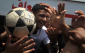 Palestinian football player Mahmud Sarsak who staged a hunger strike of nearly three months while in Israeli jail is greeted by supporters as he...