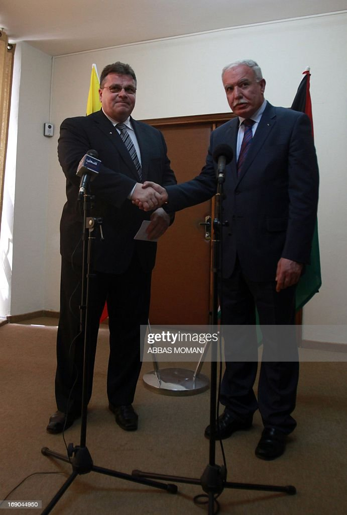 Palestinian foreign minister Riyad al-Malki (R) and his Lithuanian counterpart Linas Linkevicius shake hands following a press conference in the city of Ramallah on May 19, 2013. AFP PHOTO/ ABBAS MOMANI