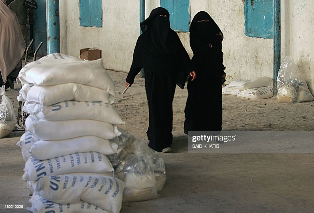 Palestinian fully veiled women walk past bags of wheat flour at an aid distribution centre of the United Nations Relief and Works Agency (UNRWA) in Rafah in the southern Gaza Strip on September 10, 2013.