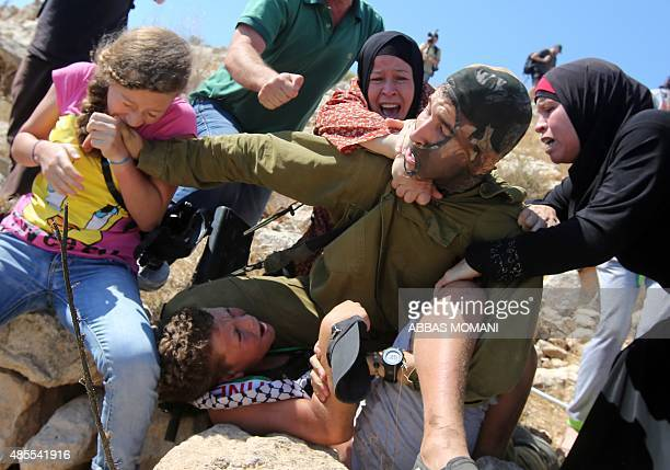 A Palestinian girl and women figth to free a Palestinian boy held by an Israeli soldier during clashes between Israeli security forces and...