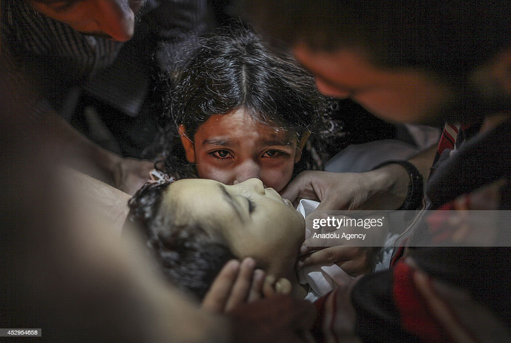 Palestinian girl Ansam says goodbye to her little brother Sameh Junaid killed in an Israeli cannon shot within the 'Operation Protective Edge' killed...
