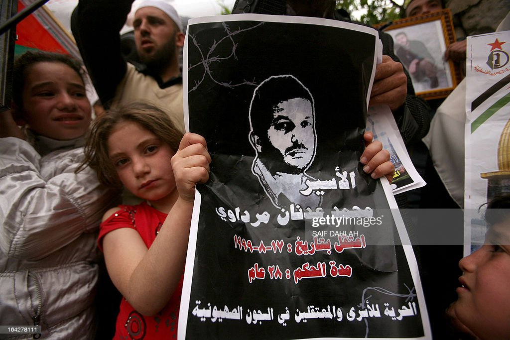 A Palestinian girl carries a placard in the northern West Bank village of Araba, near Jenin, on March 22, 2013 during a protest against the visit of US President Barack Obama to the Palestinian territories and to demanding the release Palestinian prisoners in Israeli jails.