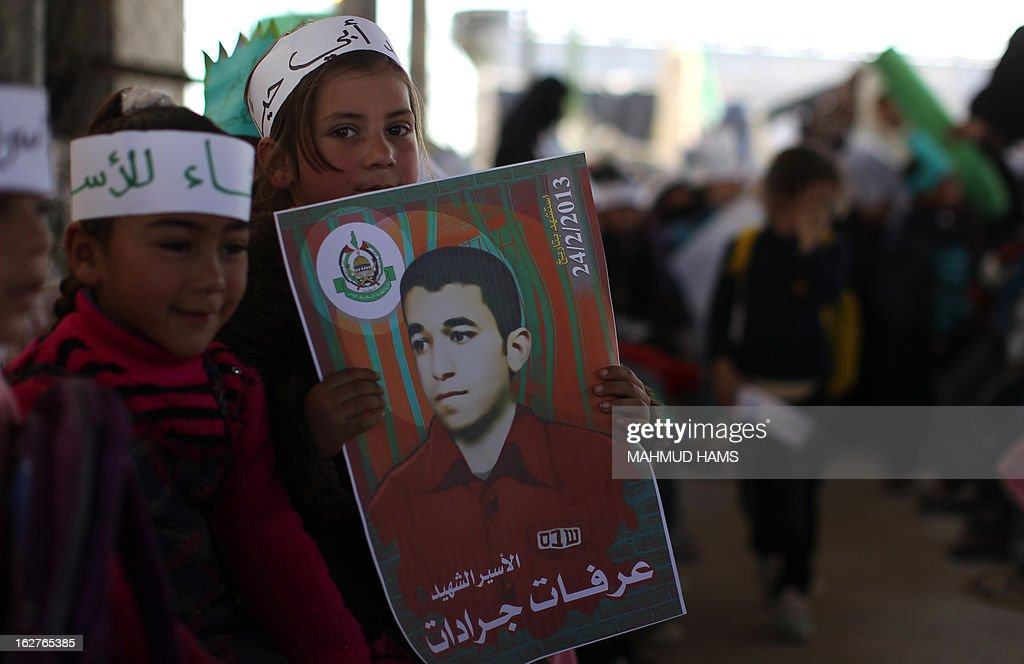 A Palestinian girl carries a poster of Arafat Jaradat, who died in an Israeli prison, during a protest at Erez border crossing between Israel and the northern Gaza Strip on February 26, 2013. Gaza militants from Fatah's Al-Aqsa Martyrs Brigades fired a rocket at Israel as a 'preliminary response' after one of its members died in an Israeli jail. AFP PHOTO / MAHMUD HAMS