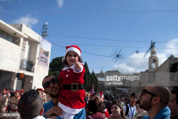 Palestinian girl dressed in a Santa Claus costume is seen outside the Church of the Nativity on December 24 2014 in Bethlehem West Bank Every...