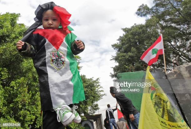 A Palestinian girl dressed in the colours of the national flag with Fatah movement's emblem is held by a protester during a demonstration by Lebanese...