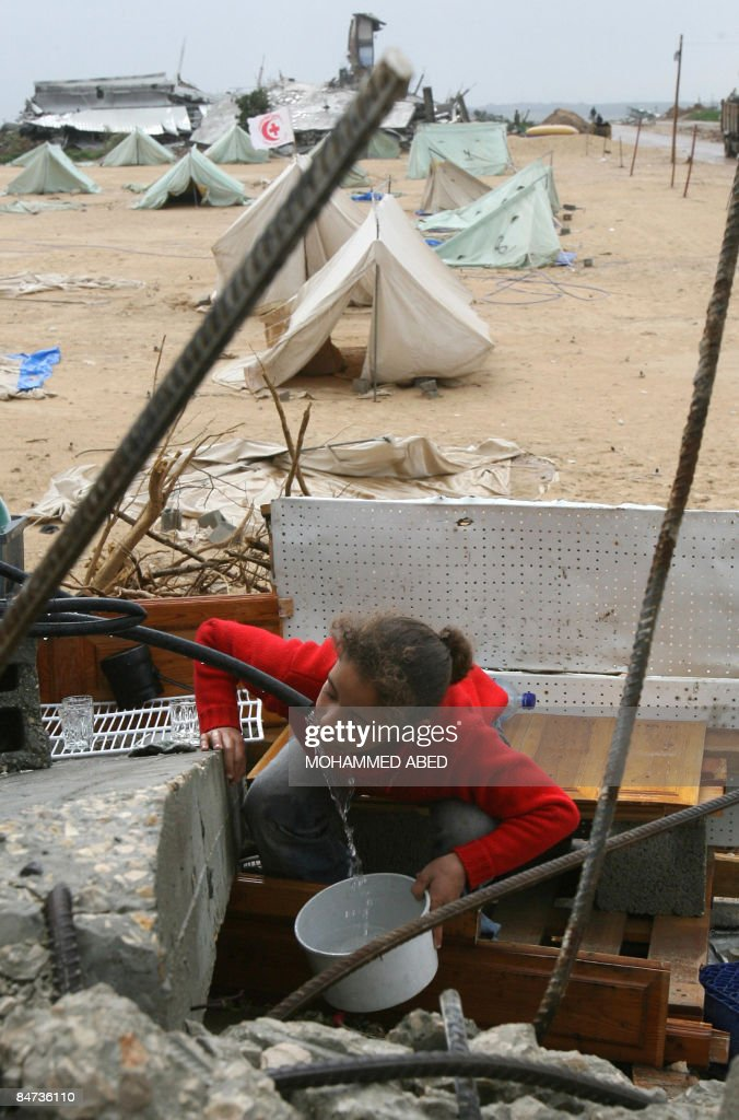 A Palestinian girl drinks water from a water tank installed near tents of Palestinian people who lost their houses during Israel�s 22day military...